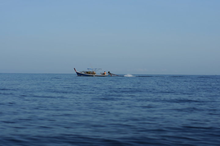 The calm Andaman Sea with a traditional Thai Longtail boat